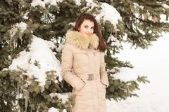 Young woman in winter park. Portrait of woman in winter park near the winter tree Stock Photo