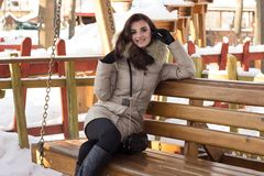 Young woman in winter park sitting on bench. With a lot of snow around Stock Images
