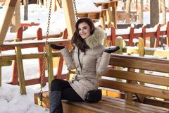 Young woman in winter park sitting on bench. With a lot of snow around Stock Photo