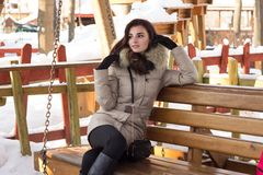 Young woman in winter park sitting on bench Stock Photos
