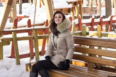 Young woman in winter park sitting on bench Royalty Free Stock Images