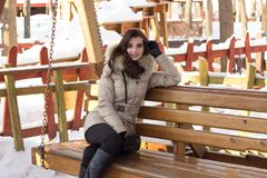 Young woman in winter park sitting on bench. With a lot of snow around Stock Photos