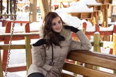 Young woman in winter park sitting on bench. With a lot of snow around Royalty Free Stock Images