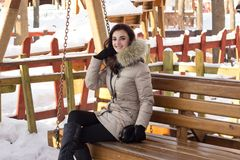 Young woman in winter park sitting on bench. With a lot of snow around Royalty Free Stock Photos