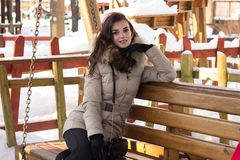 Young woman in winter park sitting on bench. With a lot of snow around Royalty Free Stock Image