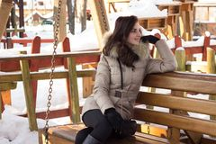 Young woman in winter park sitting on bench. With a lot of snow around Stock Photography