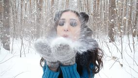 Concept of winter entertainment. Young woman in winter park with snow in hands stock video