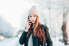 Young woman in winter park talking mobile phone Stock Images