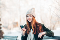 Young woman in winter park talking mobile phone Stock Image
