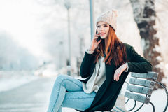 Young woman in winter park talking mobile phone Royalty Free Stock Image
