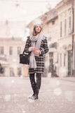 Young woman winter snowing looking above. Up. Winter fashion stylish clothes, scarf, coat, hat royalty free stock image