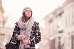 Young woman winter snowing looking above. Up. Winter fashion stylish clothes scarf, coat, hat Royalty Free Stock Photography