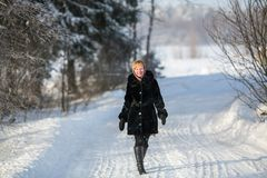 Young woman in the winter on the snowy road. At park Royalty Free Stock Images