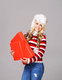 Young woman in winter wear holding a box Stock Photos