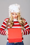 Young woman in winter wear holding a red box Stock Photography