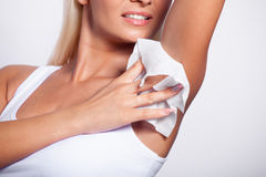 Young woman wipes the armpit with wet wipes Stock Images