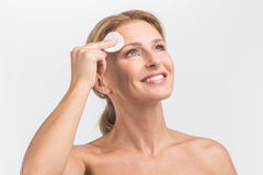 Young woman wipes face skin. Royalty Free Stock Photography