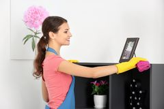 Young woman wiping dust. While cleaning flat Stock Photo