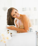 Young woman wiping hair with towel. In modern bathroom royalty free stock images