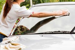 Young woman,wiping her car with microfiber cloth after washing. Stock Photo