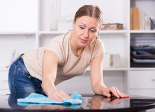 Young woman wiping table Royalty Free Stock Images