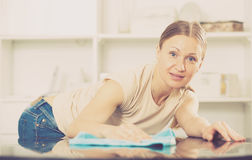 Young woman wiping table Stock Image