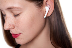 Young woman with wireless earphones. Wireless earphones on human hands. studio shot Royalty Free Stock Photography