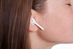 Young woman with wireless earphones Stock Images