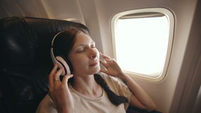 Young woman in wireless headphones listening to music and smiling during fly in airplane. Young woman in wireless headphones listening to music and smiling stock footage