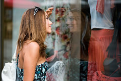 Young woman wistfully looking at the clothes. In the shop window Royalty Free Stock Image