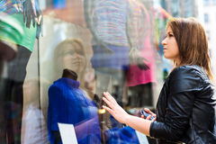 Young woman wistfully looking at the clothes Stock Photo