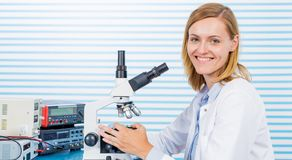 Young woman witch blonde long hair testing blood on RBC, HGB HCT. laboratory bench which blood sample and microscope stock image