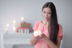 Free Young Woman With A Decorative Candle On A Background Of A Bright Living Room Royalty Free Stock Photography - 114053577
