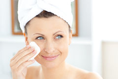 Young Woman With A Towel Putting Cream On Her Face Royalty Free Stock Photos