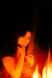 Young Woman With Bass Guitar And Flames Royalty Free Stock Image
