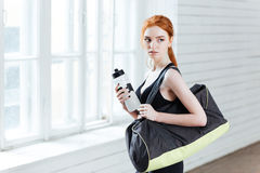 Young Woman With Bottle Of Water And Sports Bag Stock Photo