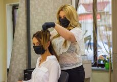Free Young Woman With Hair Rollers, Young Woman In The Hairdresser Salon, The Hairdresser With Black Protective Mask Decorates The Clie Royalty Free Stock Photos - 184241418