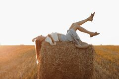 Free Young Woman With Long Hair, Wearing Jeans Skirt, Light Shirt Is Lying On Straw Bale In Field In Summer On Sunset. Female Royalty Free Stock Images - 217224949