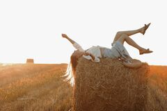 Free Young Woman With Long Hair, Wearing Jeans Skirt, Light Shirt Is Lying On Straw Bale In Field In Summer On Sunset. Female Stock Photos - 217965403