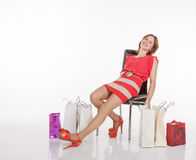 Young Woman With Shopping Bags Sits On A Chair Royalty Free Stock Photo