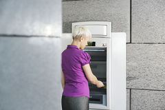 Young woman withdrawing money with card at atm Stock Image