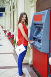Young woman withdrawing money from credit card at ATM Royalty Free Stock Image
