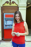 Young woman withdrawing money from credit card at ATM Royalty Free Stock Photos
