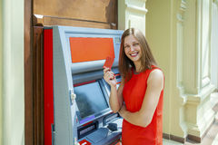 Young woman withdrawing money from credit card at ATM Stock Photography