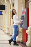 Young woman withdrawing money from credit card at ATM Royalty Free Stock Images