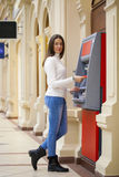 Young woman withdrawing money from credit card at ATM Stock Photo