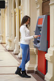 Young woman withdrawing money from credit card at ATM Stock Image