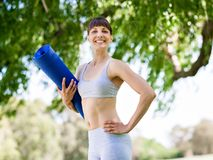 Young woman witth a gym mat in the park Royalty Free Stock Images
