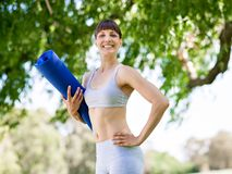 Young woman witth a gym mat in the park Royalty Free Stock Image