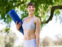 Young woman witth a gym mat in the park Stock Images